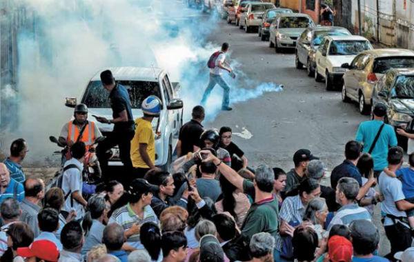 ATAQUE. Personas desconocidas lanzaron ayer gas lacrimógeno en un mitin de Juan Guaidó. Foto: AFP